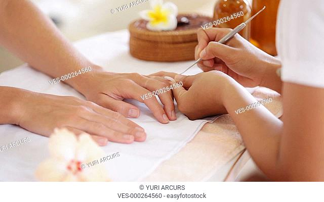 Close up footage of a beautician using a tool to carefully groom a client,s nails