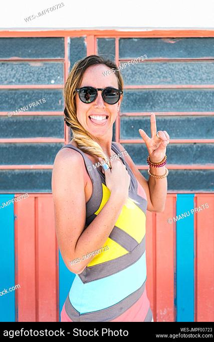 Cheerful woman sticking out tongue while peace gesturing against wall