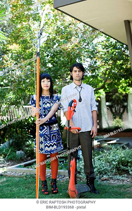Couple working in garden with tree and weed trimmers