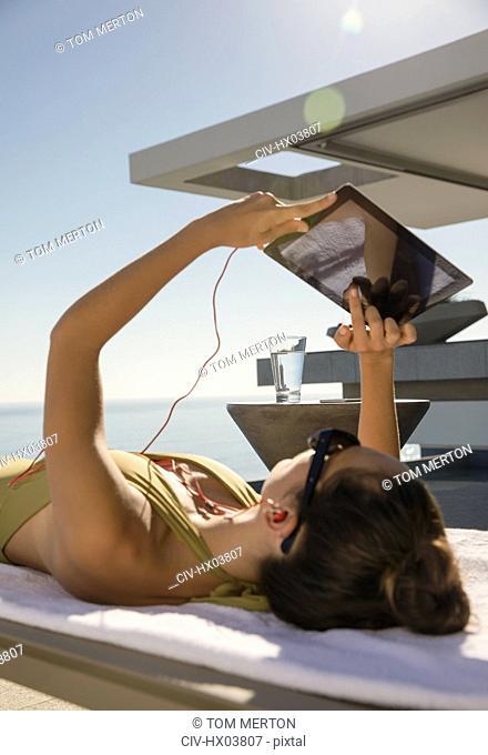 Woman sunbathing, using digital tablet on lounge chair on sunny patio