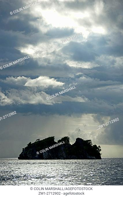 Island silhouette with dark clouds at sunset, Raja Ampat (4 Kings) area, West Papua, Indonesia