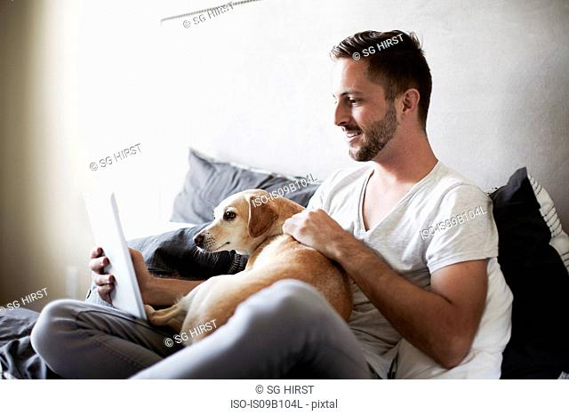 Young man and dog browsing digital tablet on bed
