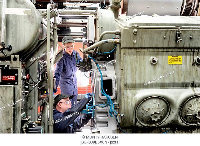 Apprentice watching engineer working on locomotive engine in train works