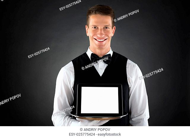 Young Butler Holding Tray With Blank Display Digital Tablet
