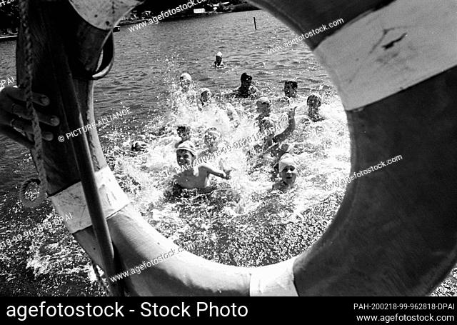 07 July 1989, Saxony, Torgau: In the summer of 1989, children can be seen in the water of a forest pool near Torgau through a life belt