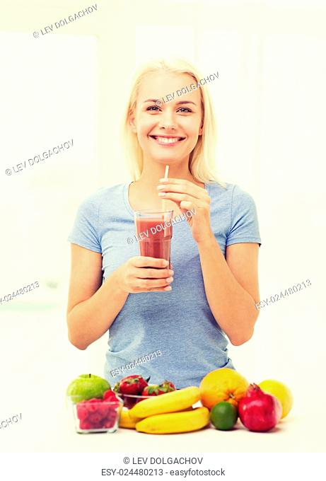 healthy eating, vegetarian food, dieting and people concept - smiling woman drinking fruit shake from glass at home
