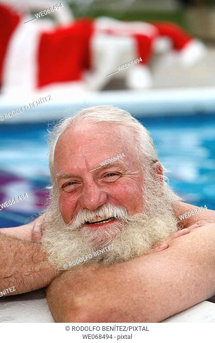 Santa smiles on the side of a swimming pool
