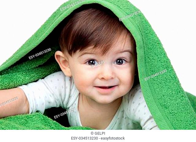 Happy baby covered with a green towel isolated on white background