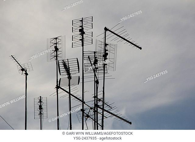 Tv aerials antennas on top of roof in city town in Rome, Italy