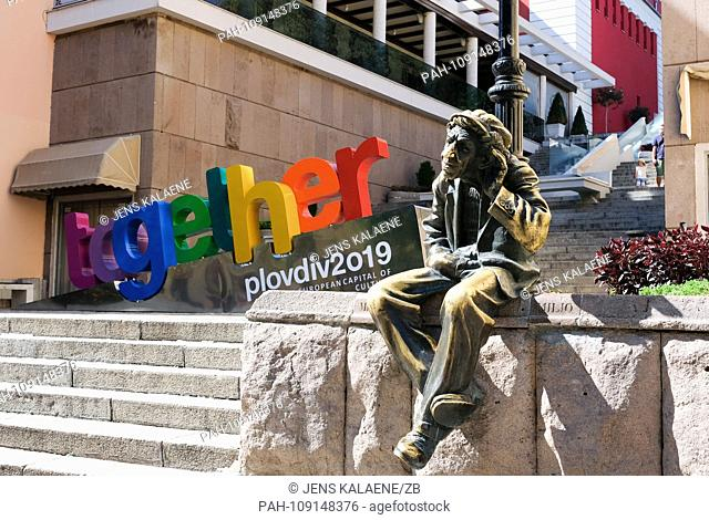 "14.09.2018, Bulgaria, Plovdiv: The sculpture """"Milyo the Crazy"""" and the word """"together"""" as motto of the cultural capital Plovdiv"