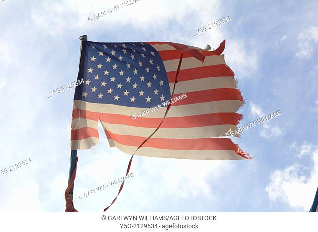 damaged american flag flying in the wind