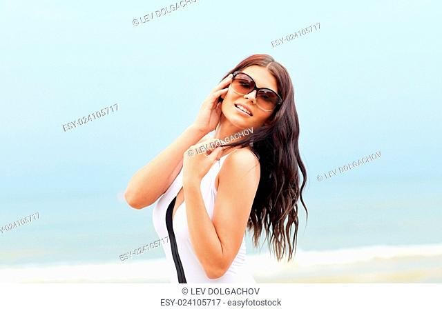 summer vacation, tourism, travel, holidays and people concept -smiling young woman in swimsuit with sunglasses on beach