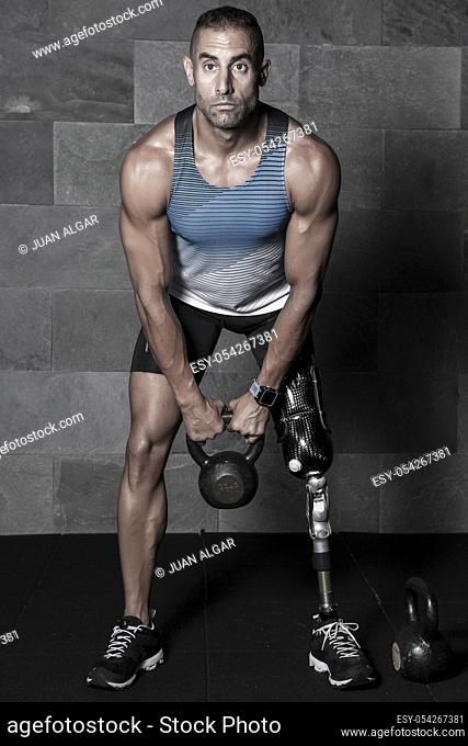 Confident muscular athlete with artificial leg limb doing squats with kettlebell in gym