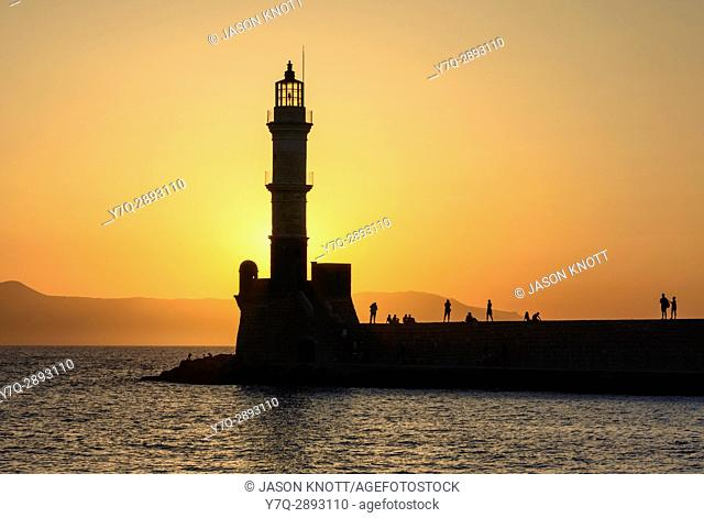 Chania, Crete sunset silhouette over the lighthouse at the entrance to the Venetian harbour wall of Hania, Crete, Greece