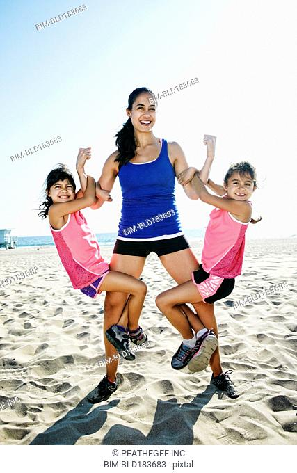 Strong mother lifting daughters at beach