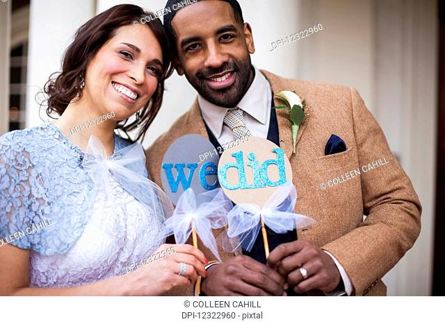 A bride and groom pose with signs symbolizing their wedding vows; Portland, Oregon, United States of America