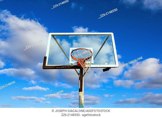 Basketball hoop and backboard with clouds overhead. San Diego, California, United States