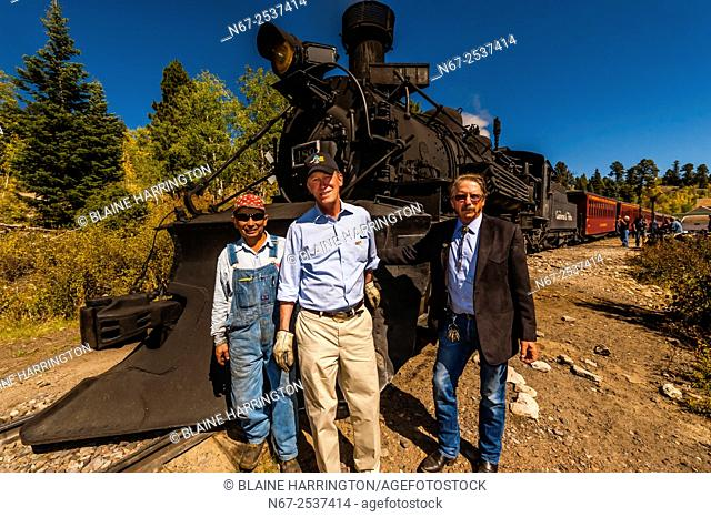 Hickenlooper with C&TSRR President John Bush and train crew. aboard the Cumbres & Toltec Scenic Railroad train, during a visit riding from Antonito to Osier
