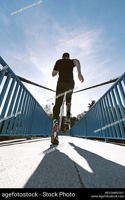 Rear view of disabled athlete with leg prosthesis running on a bridge