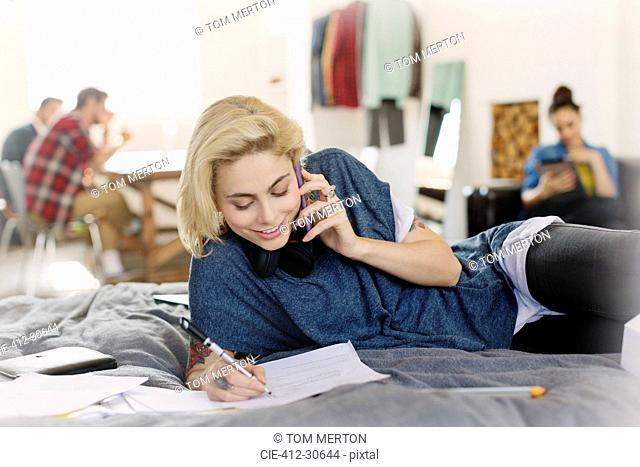 Female college student studying and talking on cell phone on bed