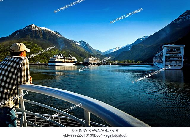 An Alaska Marine Highway ferry passenger looking at the port of Skagway crowded with four moored cruiseships, Southeast Alaska, Summer