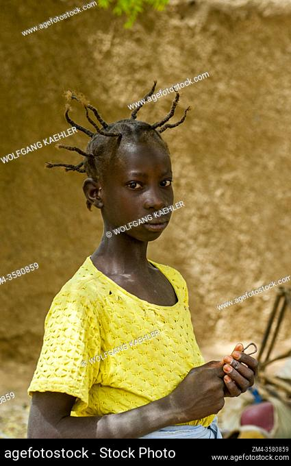 Portrait of a teenage girl with an interesting hairstyle in Segoukoro village (Bambara tribe) near Segou city in the center of Mali, West Africa