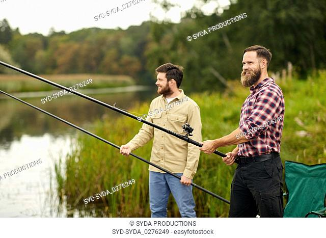 friends with fishing rods at lake or river