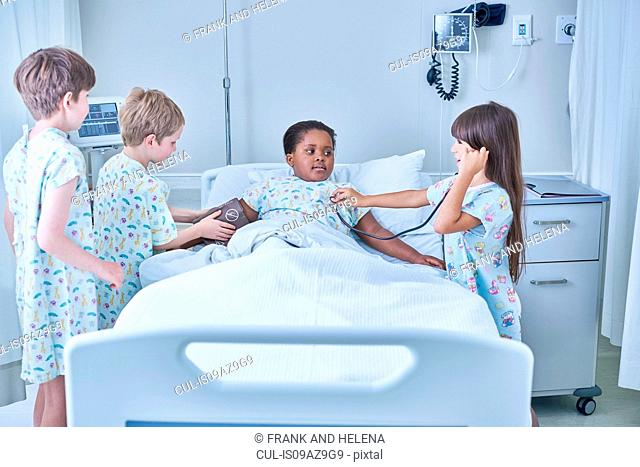 Girl and boy patients playing at treating friend in bed on hospital children's ward