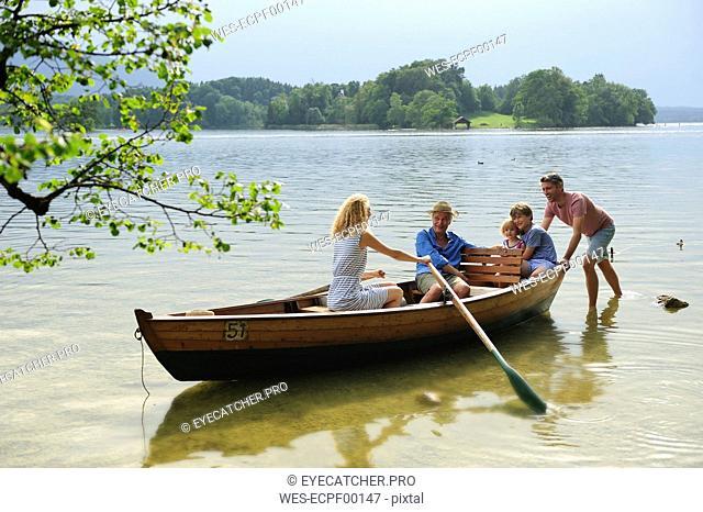 Germany, Bavaria, Murnau, family in rowing boat at lakeshore