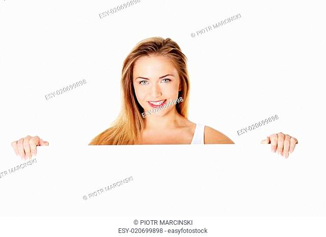 Beautiful blond teen girl behind big blank billboard