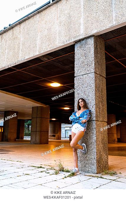 Attractive young woman in sportswear and denim jacket leaning against a column