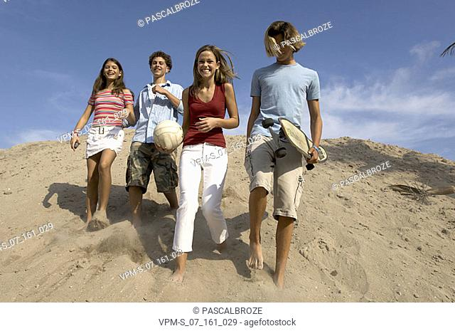 Low angle view of two teenage couples walking on the beach
