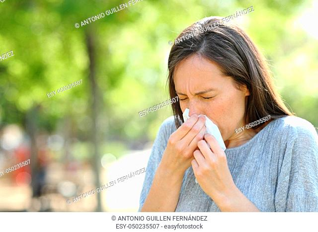 Woman sneezing using a wipe standing outdoors in a park