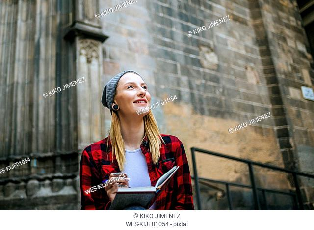 Spain, Barcelona, smiling young woman with notebook