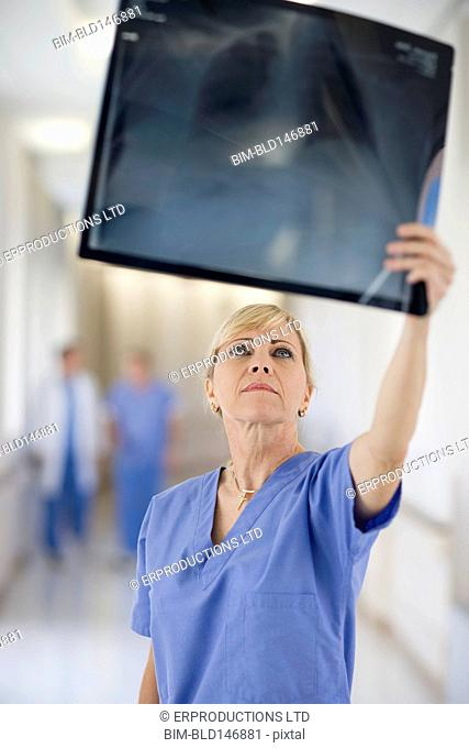 Doctor looking at x-ray in hospital corridor