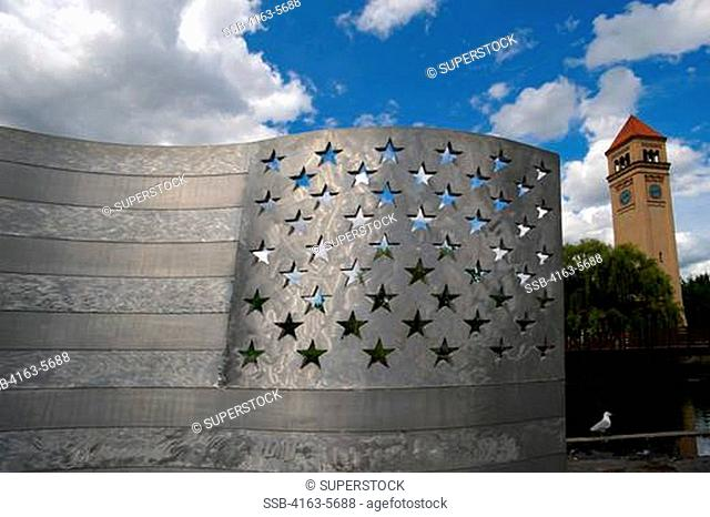 USA, WASHINGTON STATE, SPOKANE, RIVERFRONT PARK, ALUMINUM BENCH AMERICAN FLAG ART, CLOCK TOWER IN BACKGROUND