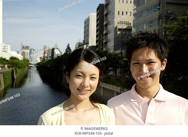 Portrait of a young couple smiling with canal in background