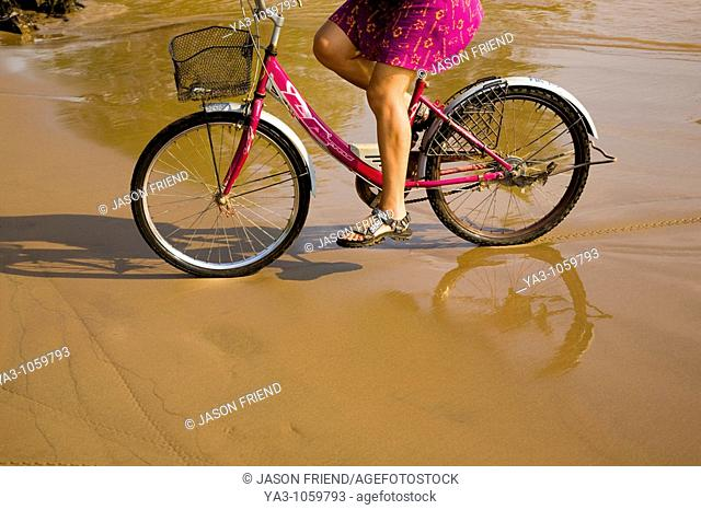 Laos, Si Phan Don Four Thousand Islands, Don Khon  Female tourist on a hired bicycle on a sandy beach on the island of Don Knon
