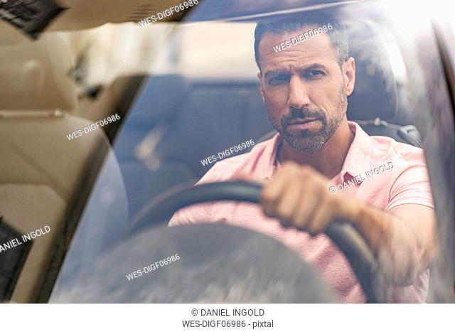 Portrait of serious man driving car