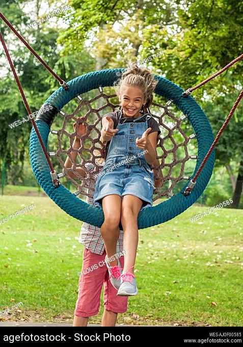 Boy pushing cheerful girl sitting on rope swing in park