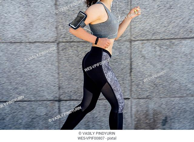 Partial view of young athletic woman running along a wall