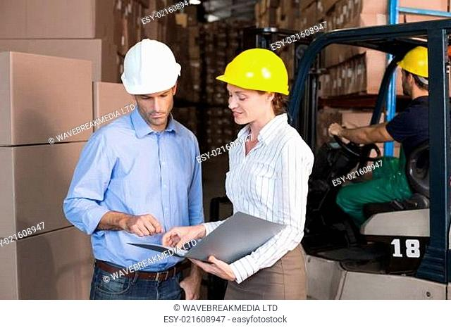 Warehouse manager talking with colleague