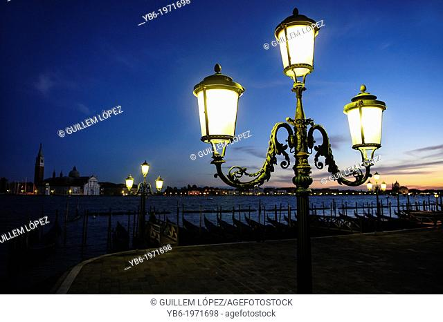 View of the Venice's waterfront with lighten up traditional street lamps, Venice, Italy