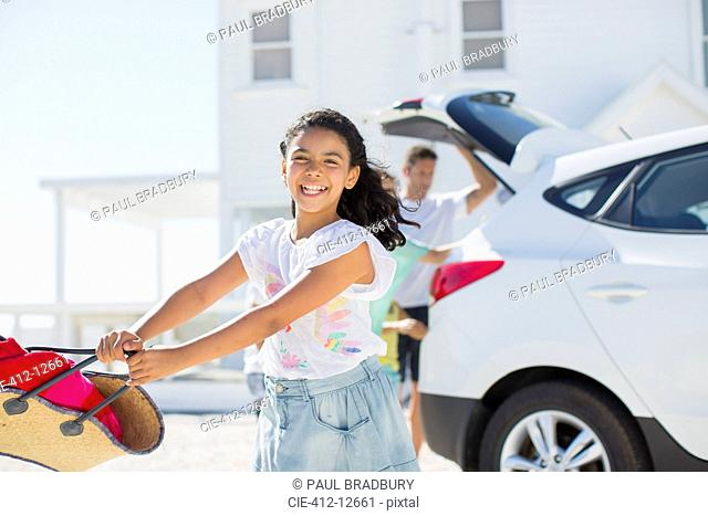 Happy girl swinging beach bag outside car in sunny driveway
