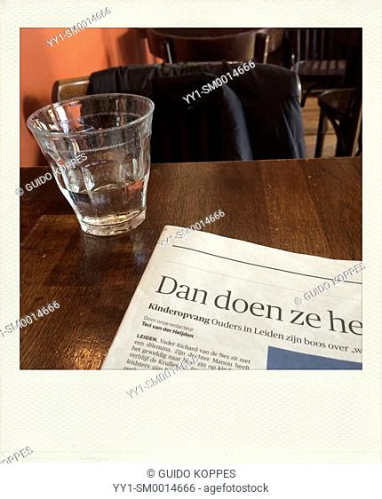 Tilburg, Netherlands. Polaroid. Glass of water and a newspaper article in front of the reader on a brown cafe table