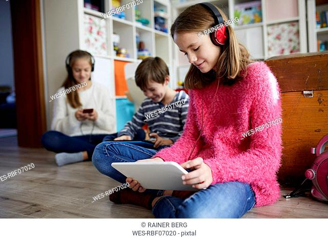 Siblings playing at home with their digital tablets, sitting on ground