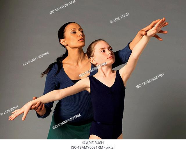 Woman teaching girl a pose
