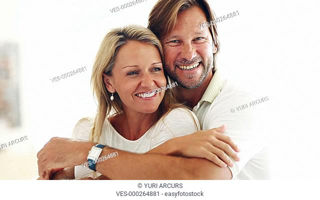 Attractive mature couple embracing lovingly and smiling