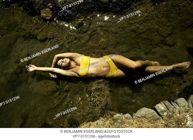 Young woman floating in sea water, Sissi, Crete, Greece