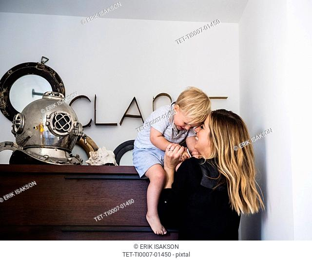 Mother holding son on top of drawers